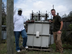 Shane with the head of the electric company in front of a 2,000 pound transformer.